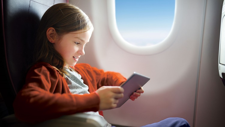 Girl on tablet inside airplane