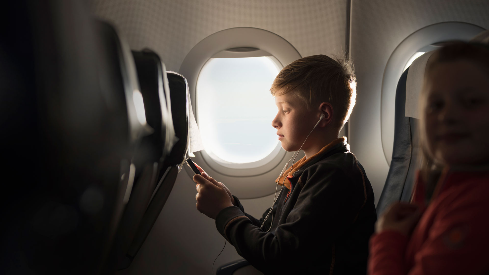 Boy using headphones connected to mobile device while seated on an airplane.