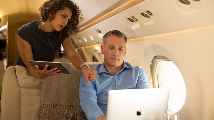 Man and woman on airplane reviewing content on a laptop computer thanks to Rockwell Collins' ARINCDirect cabin connectivity solutions.