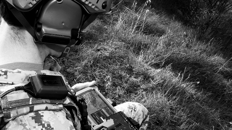 Soldier looking at his FasTAK integrated targeting system