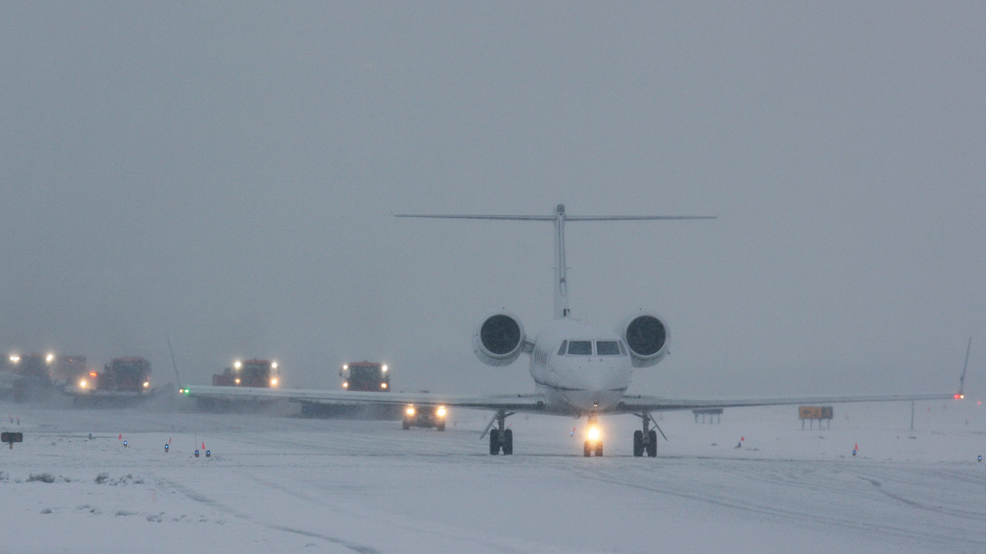 Airplane on runway in snowy conditions with snow plows