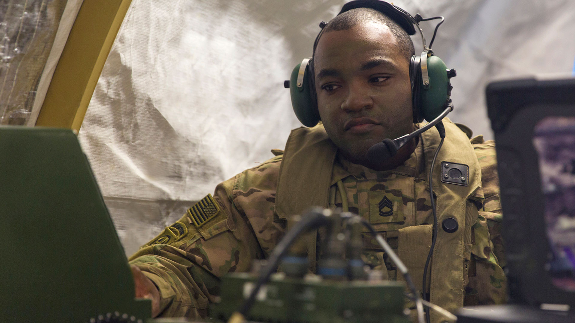 Picture of military man with a headset on using computer equipment