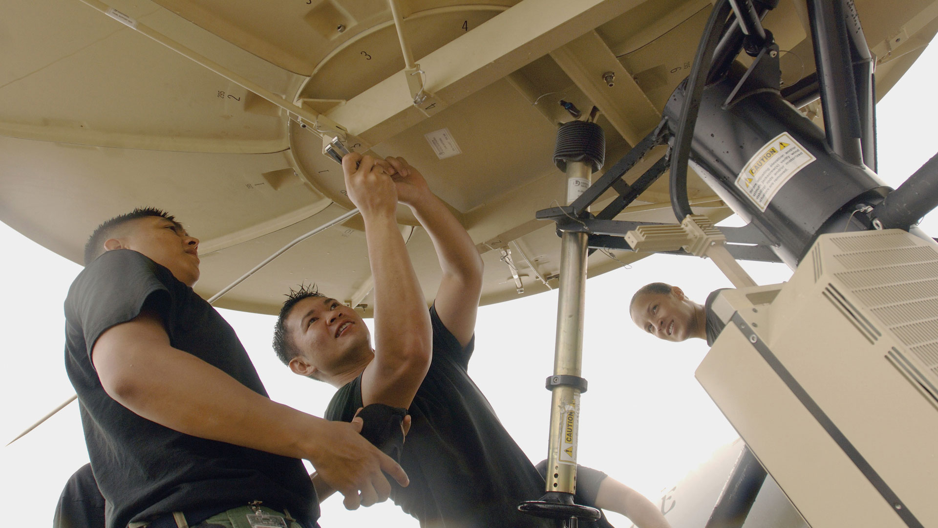 3 employees servicing satellite in the field