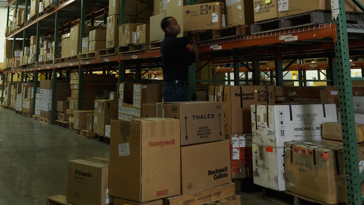Worker taking boxes off shelf