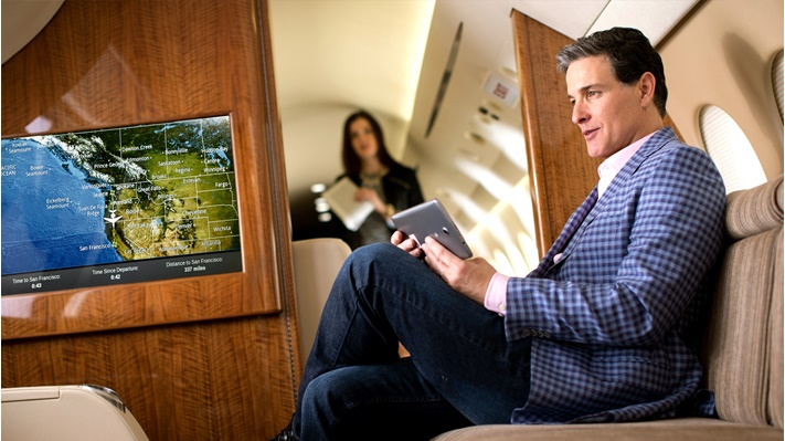 Man viewing tablet on board an aircraft. A woman stands in the background.