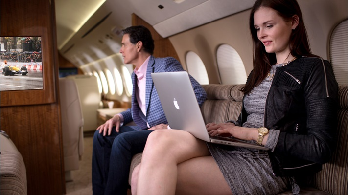 Woman viewing a latop while sitting in an aircraft cabin. A man watches television in the background.