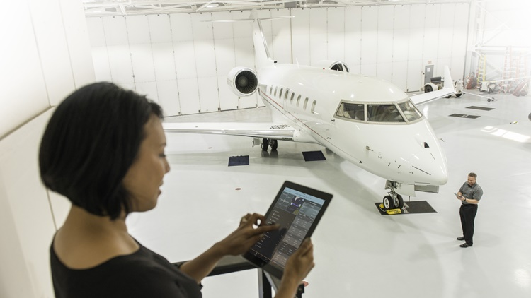 Woman reading iPad with man inspecting nose of business jet