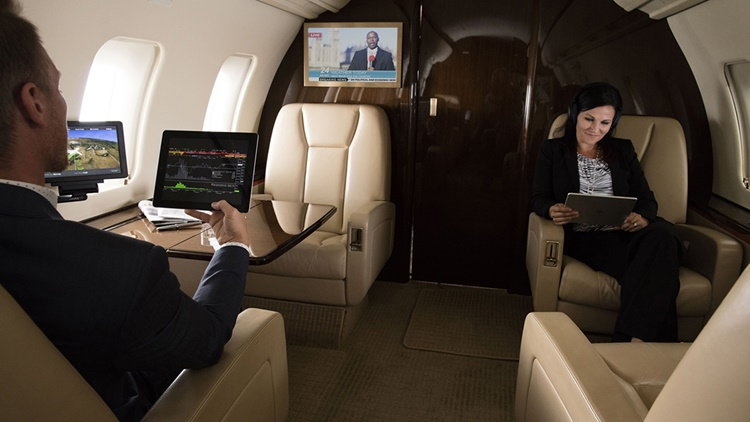Man viewing stocks on iPad and woman watching tablet while cable news plays on TV in business jet cabin