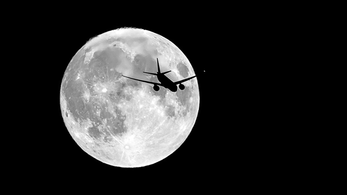 An airplane is visible against the backdrop of the moon