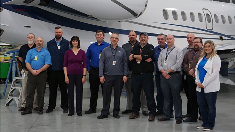 Employees standing in front of plane