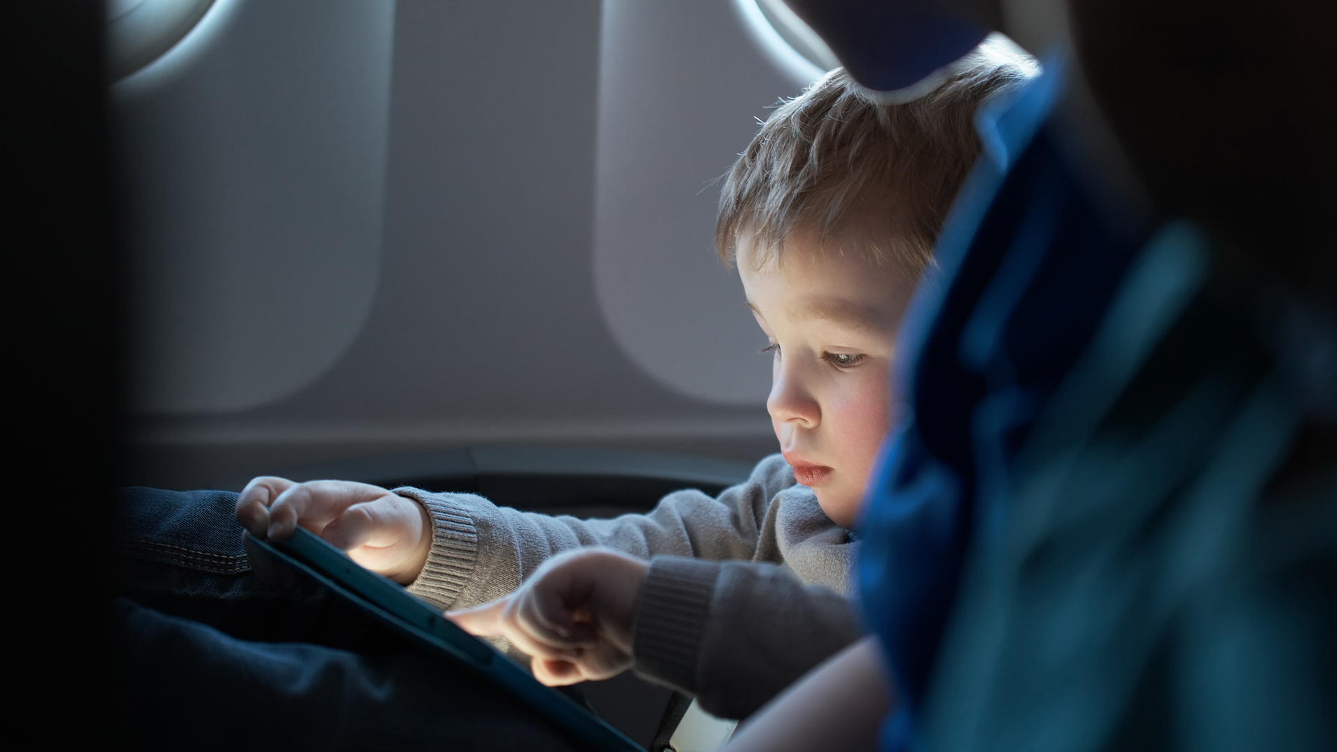 A child using a tablet on an airplane