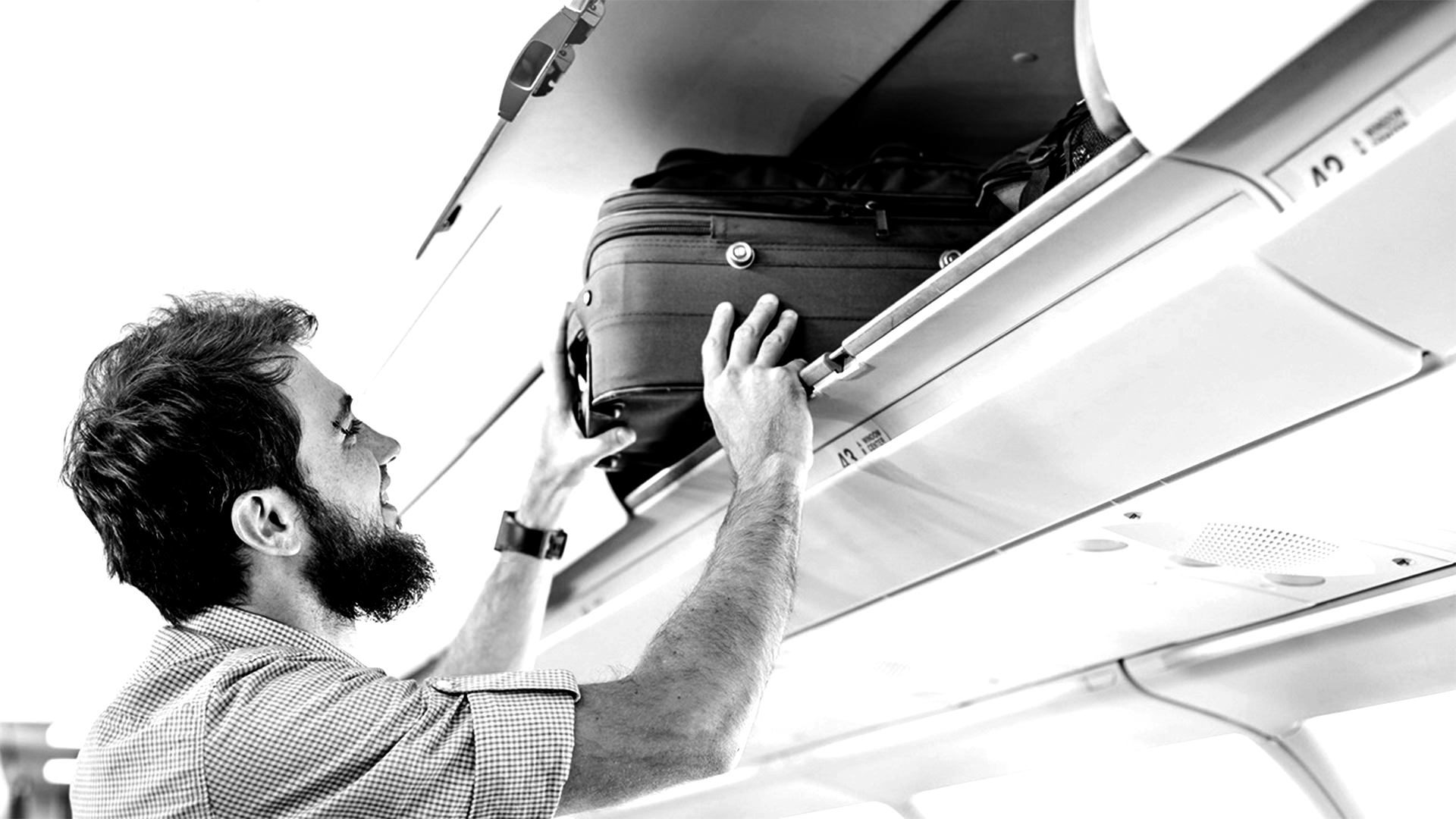 Man putting luggage in overhead bin on airplane