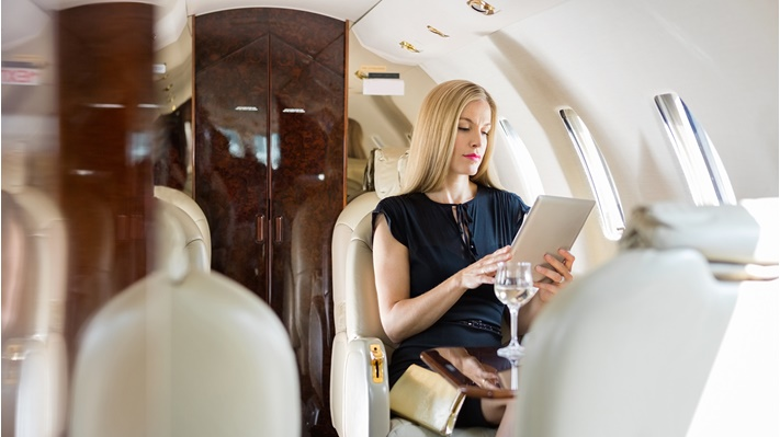 A woman uses a tablet in the aircraft cabin
