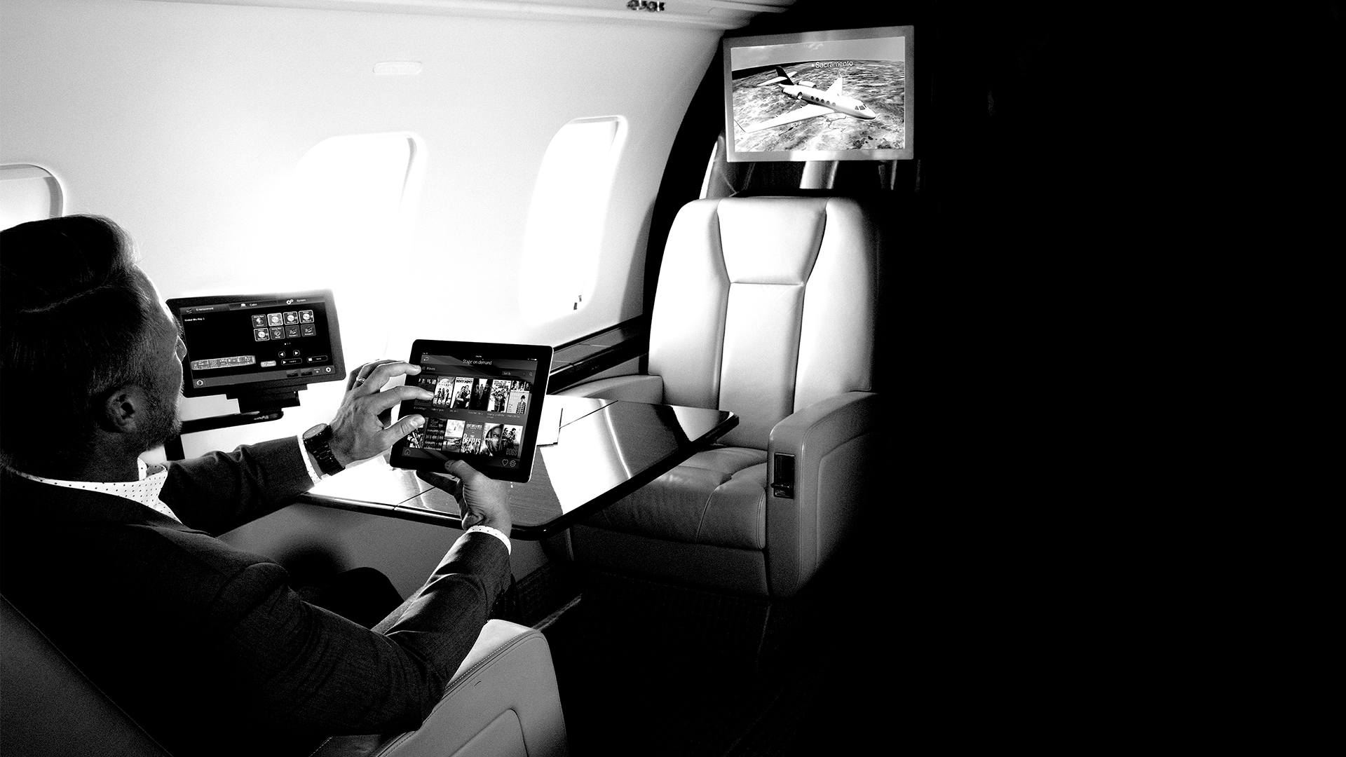 Man watching TV in the cabin of a business jet
