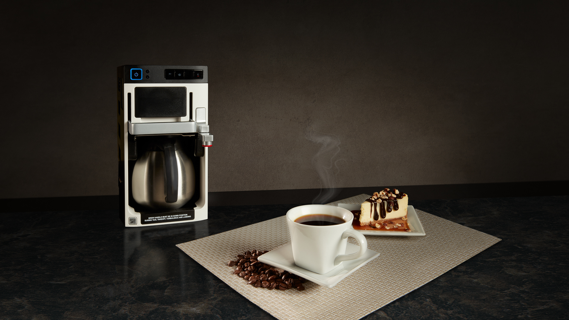 Essence beverage maker on counter with coffee and chessecake on a placemat