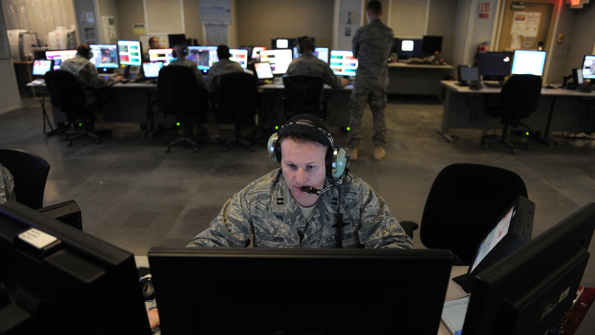 Image of man with headset in front of computer moniter