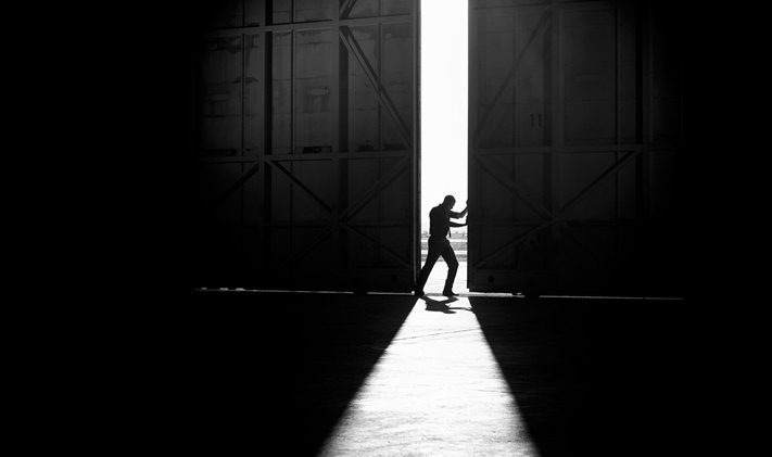 black and white hangar, man opening door