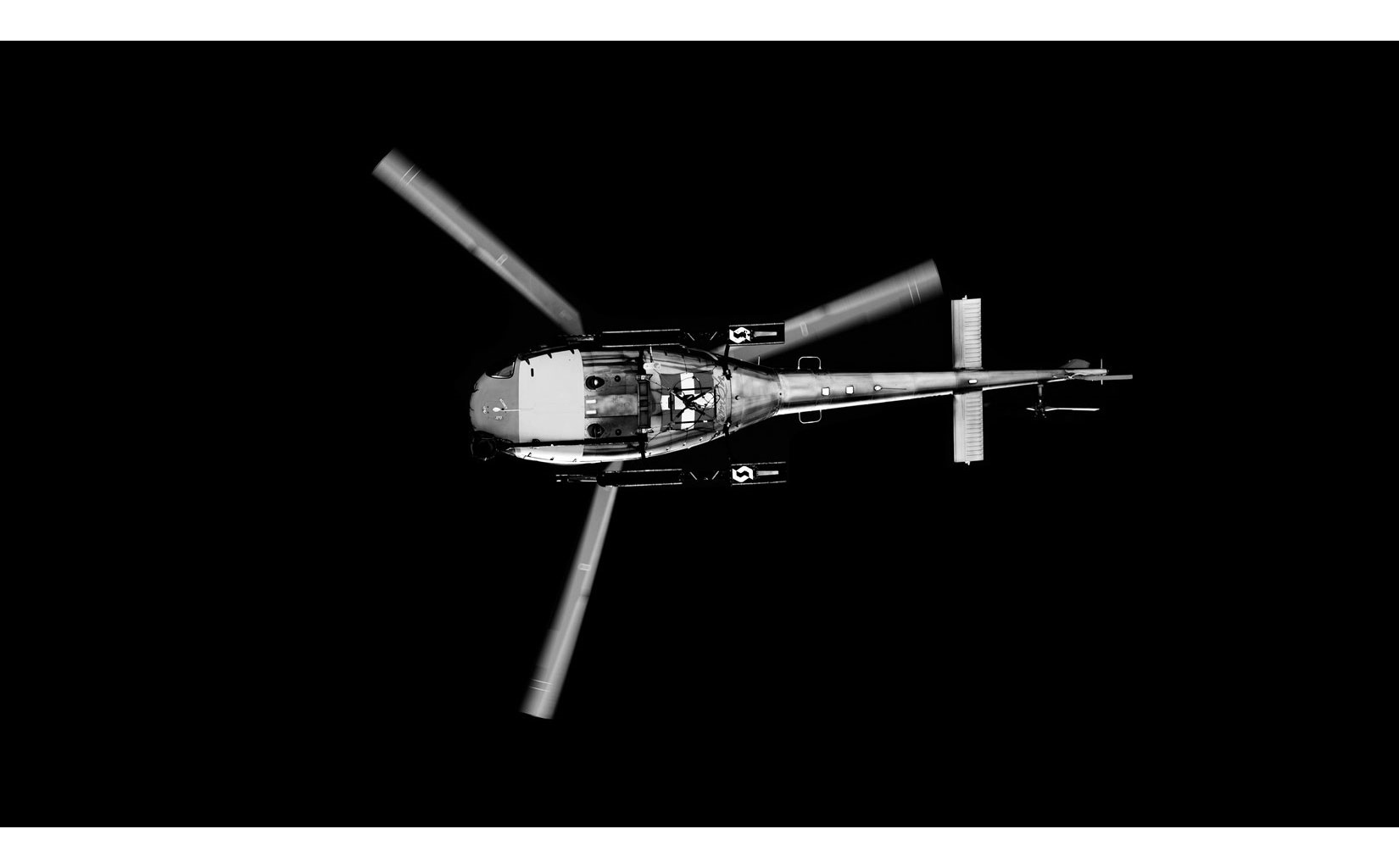 Black and white helicopter from below, showing wings in rotation