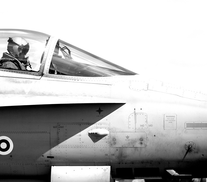 black and white fighter jet, shown from side with pilot in seat