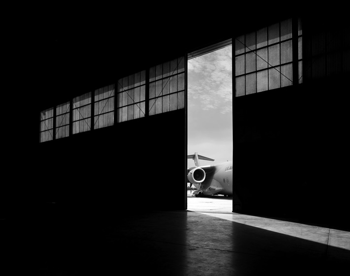 black and white military aircraft hangar with engine showing