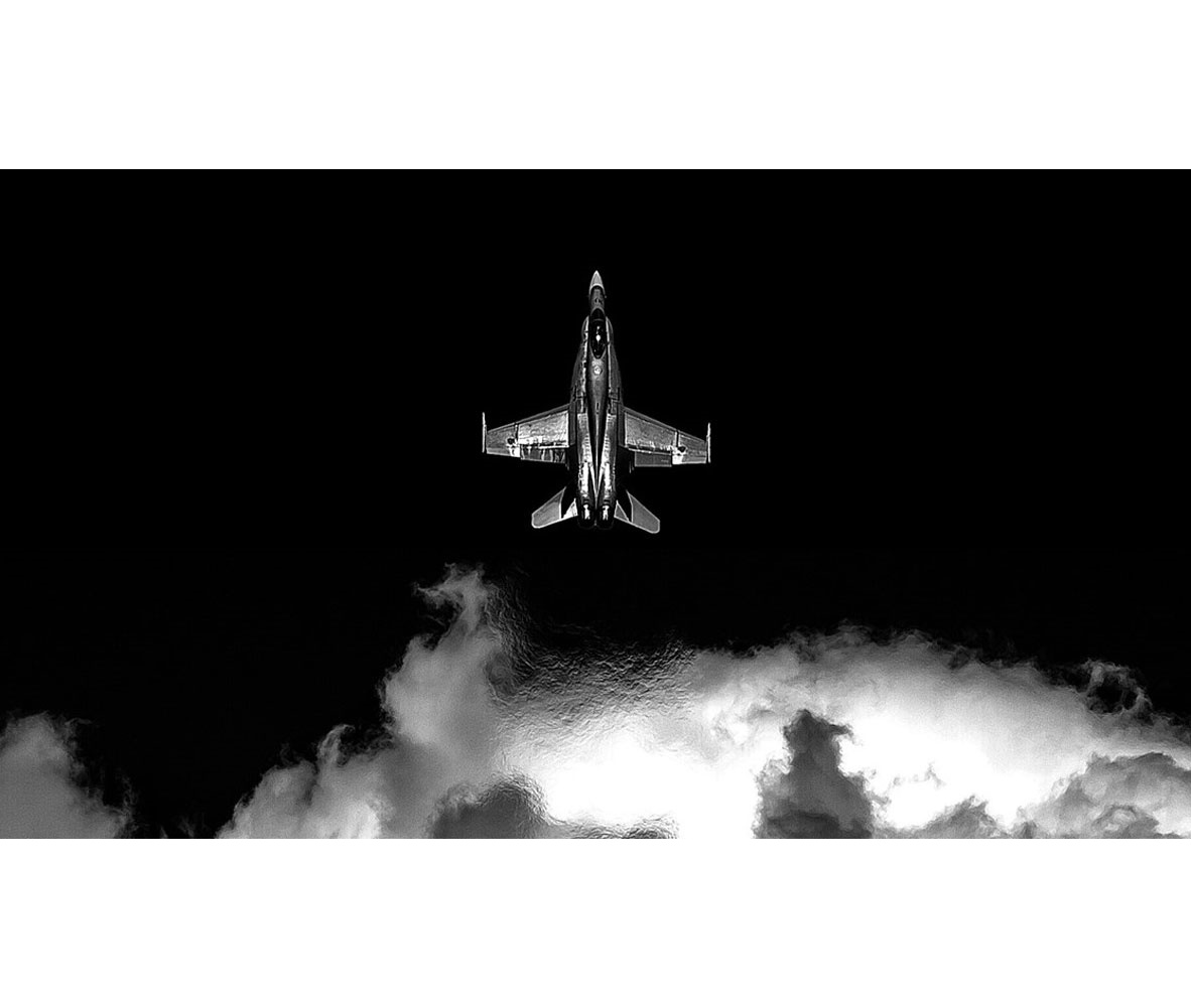 black and white military aircraft flying through clouds, aerial view