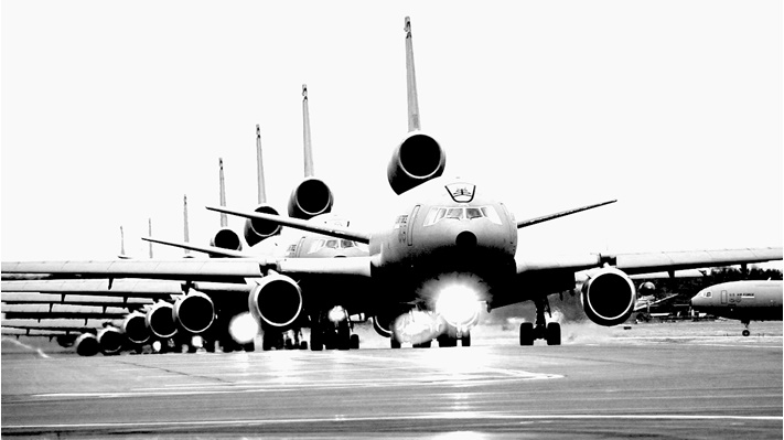 Black and white, line of KC390s getting ready to take off on runway