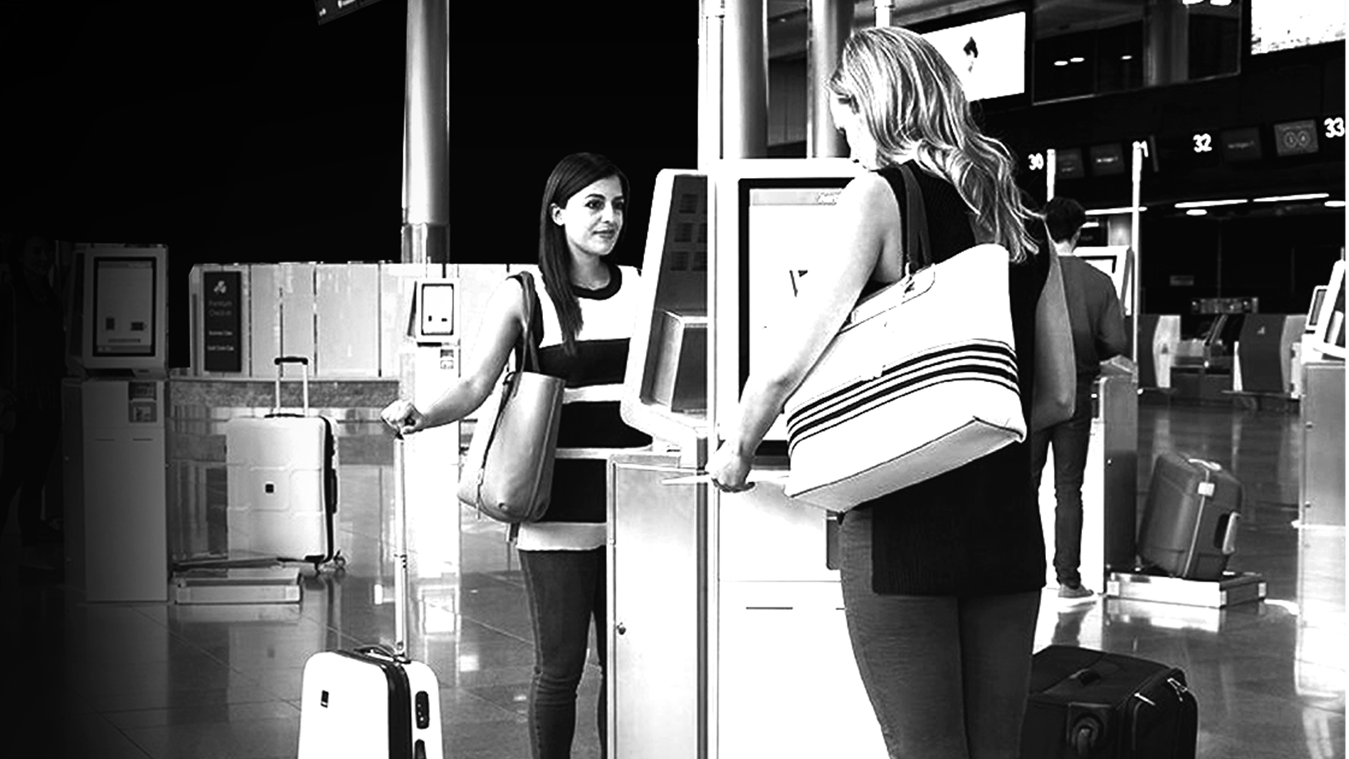 Two women using airport kiosks