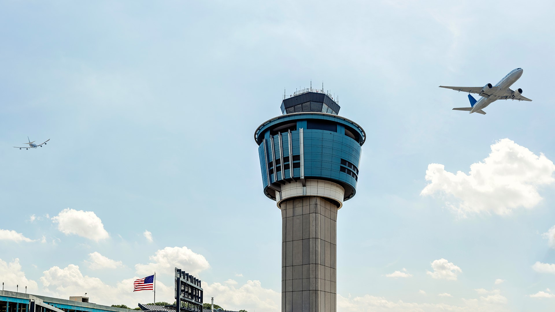 control tower with airplane in the sky