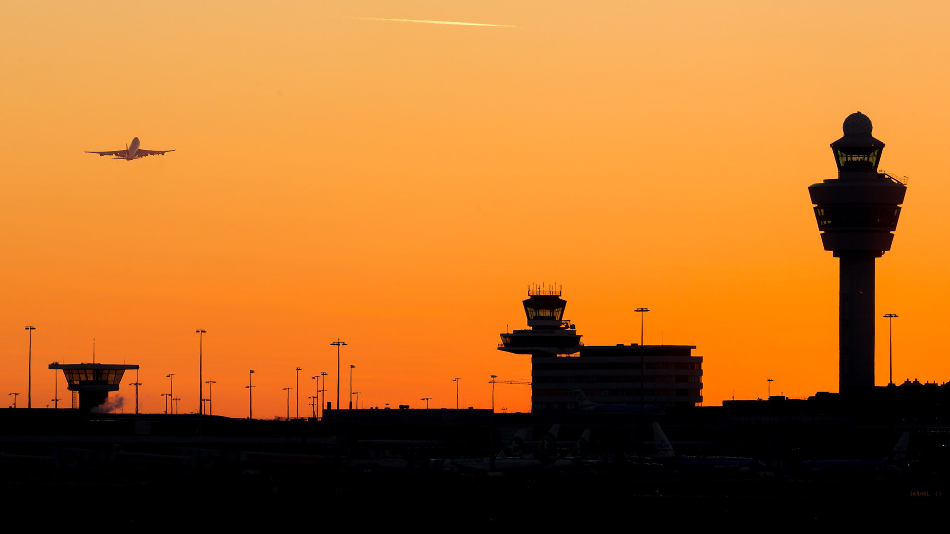 Amsterdam-Schiphol airport sunset at a clear sky with departing airplane